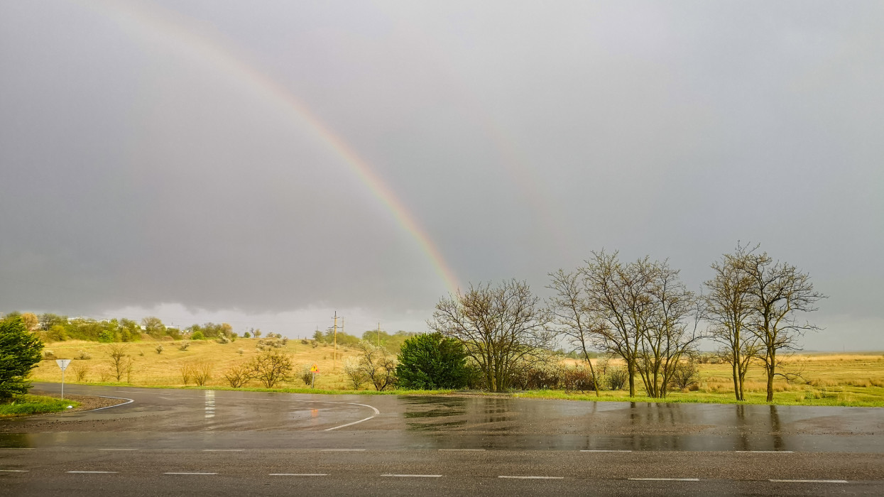 Summer landscape with rainbow after rain over road