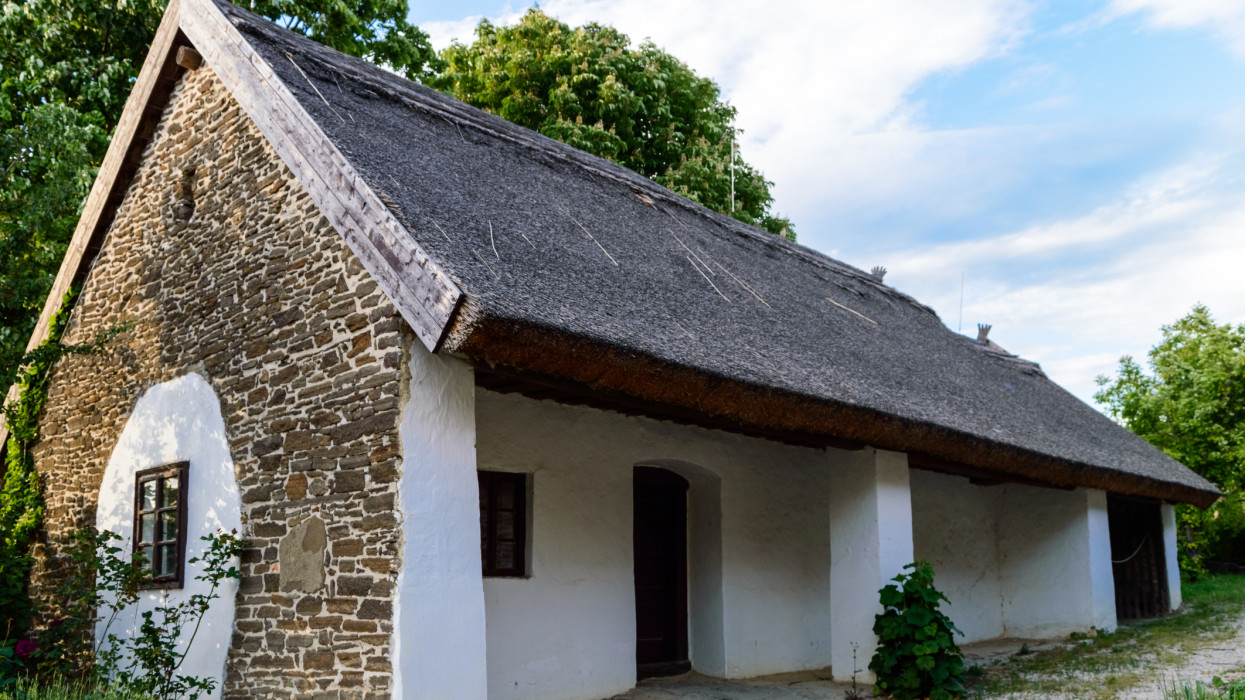 A traditional thatched house with whitewashed walls and stone facade, trees and plants in the courtyard and a blue sky in the sunset.