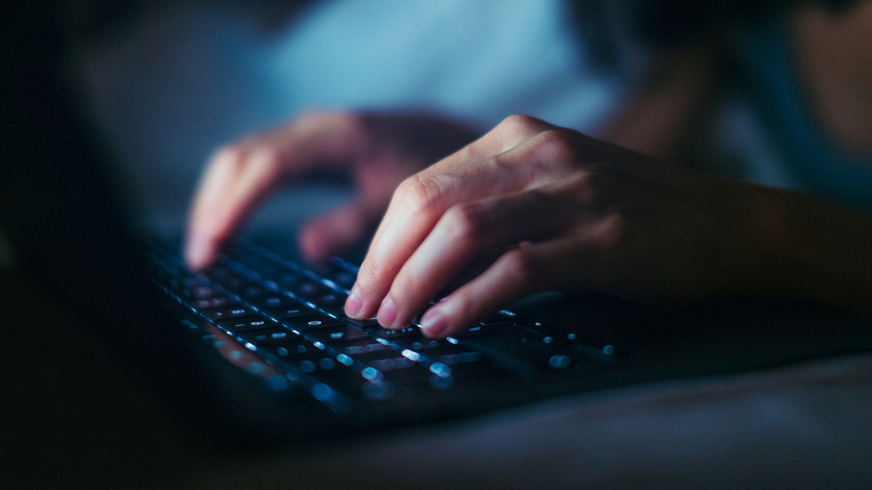 Close-up shot of female hands typing on computer keyboard, lying on bed, working late at home.