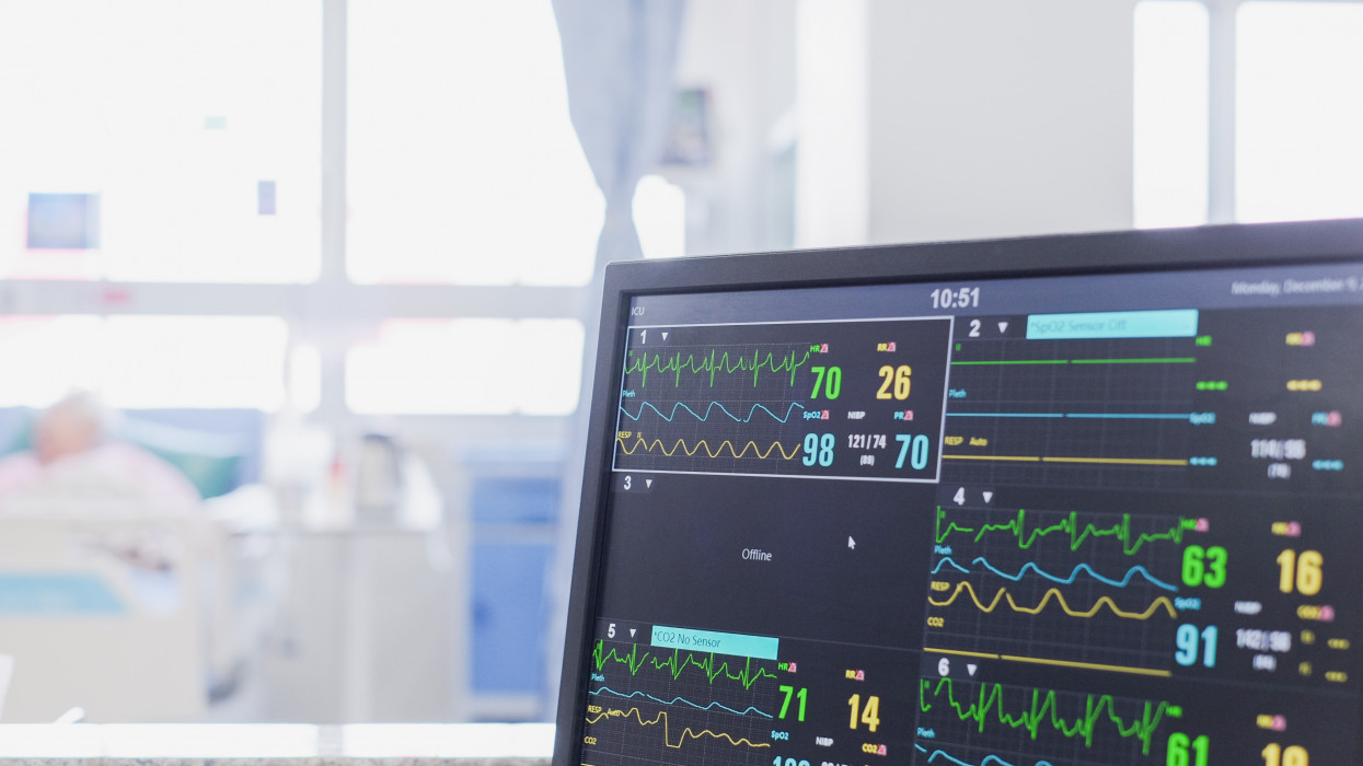 Heart rate monitor, patient and doctors in background in intensive care unit or emergency room