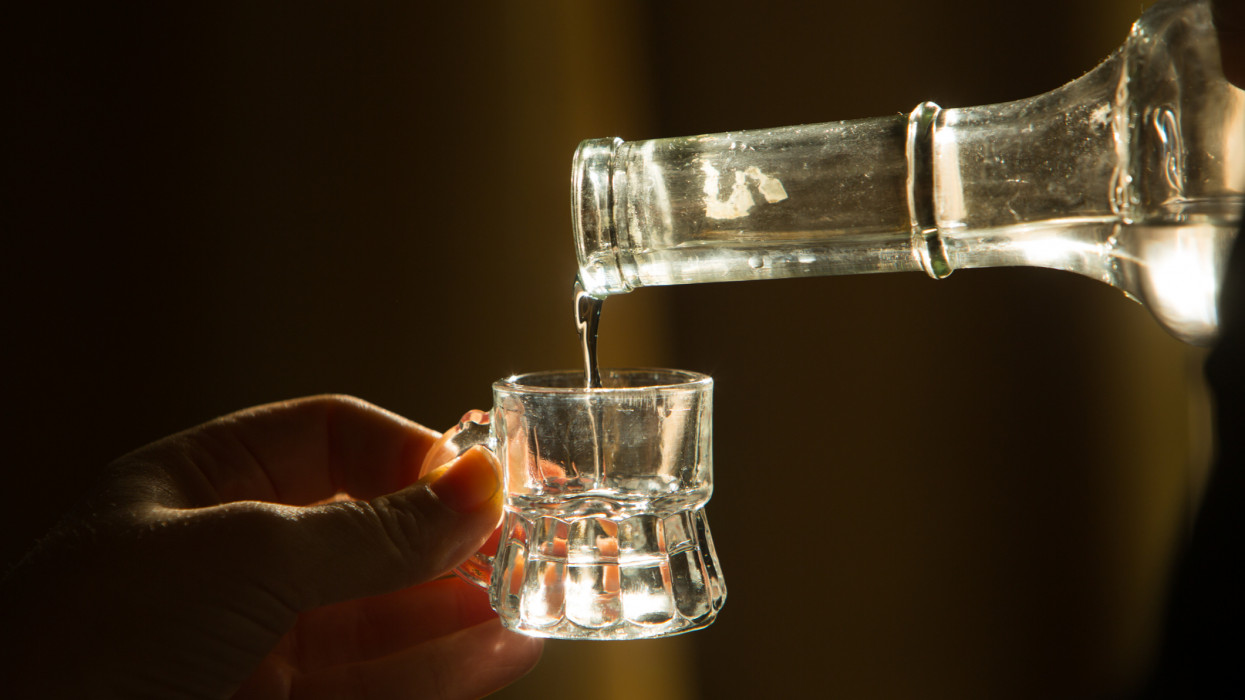 Palinka, the famous homemade Hungarian alcohol pouring from a bottle to glass. Stock photo from Hungary.