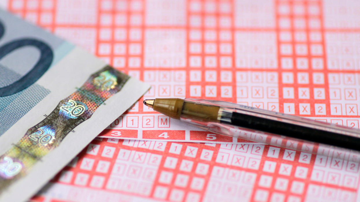 Close-Up Of Sports Betting Ticket, Euro Bills And Pen