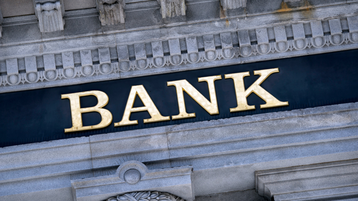 An old fashioned Bank sign on a building exterior.