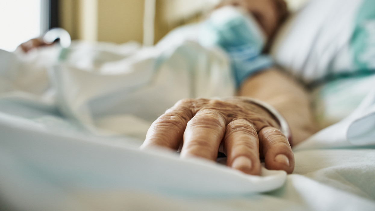 Senior woman wearing mask infected by coronavirus on hospital bed receiving medicine by drip. Close-up fingers of the senior patient ´s hand while she is sleeping. Horizontal photo