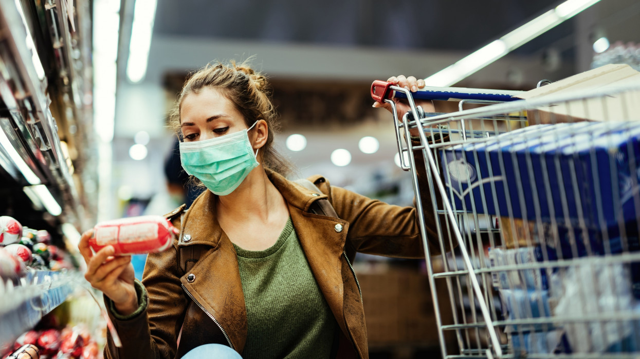 Young woman wearing protective mask and buying food in grocery store during coronavirus pandemic. cimlapi
