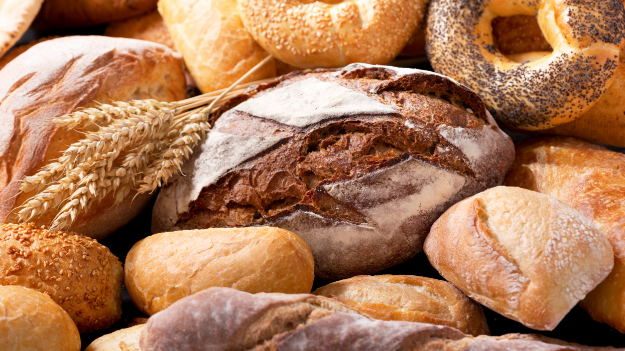 various types of fresh bread with wheat ears as background
