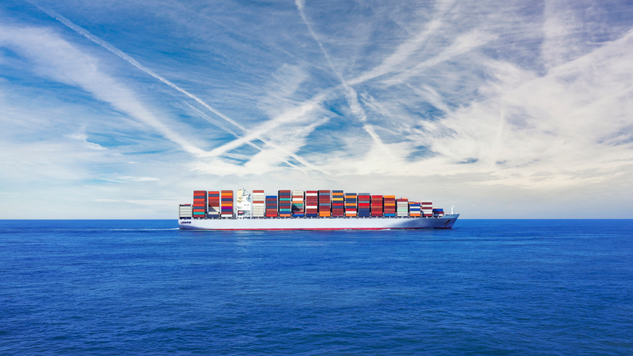 Freight transportation - A large cargo container ship transporting hundreds of multi coloured containers across the sea