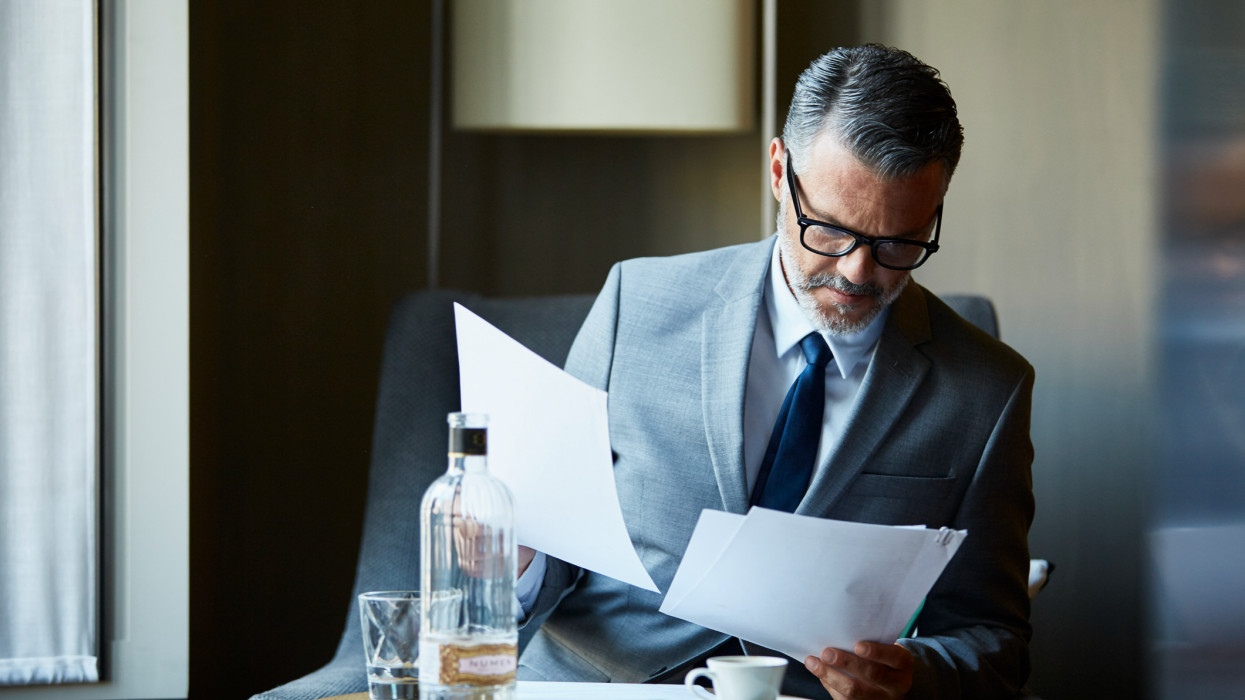 Businessman reading documents while sitting on chair in hotel room