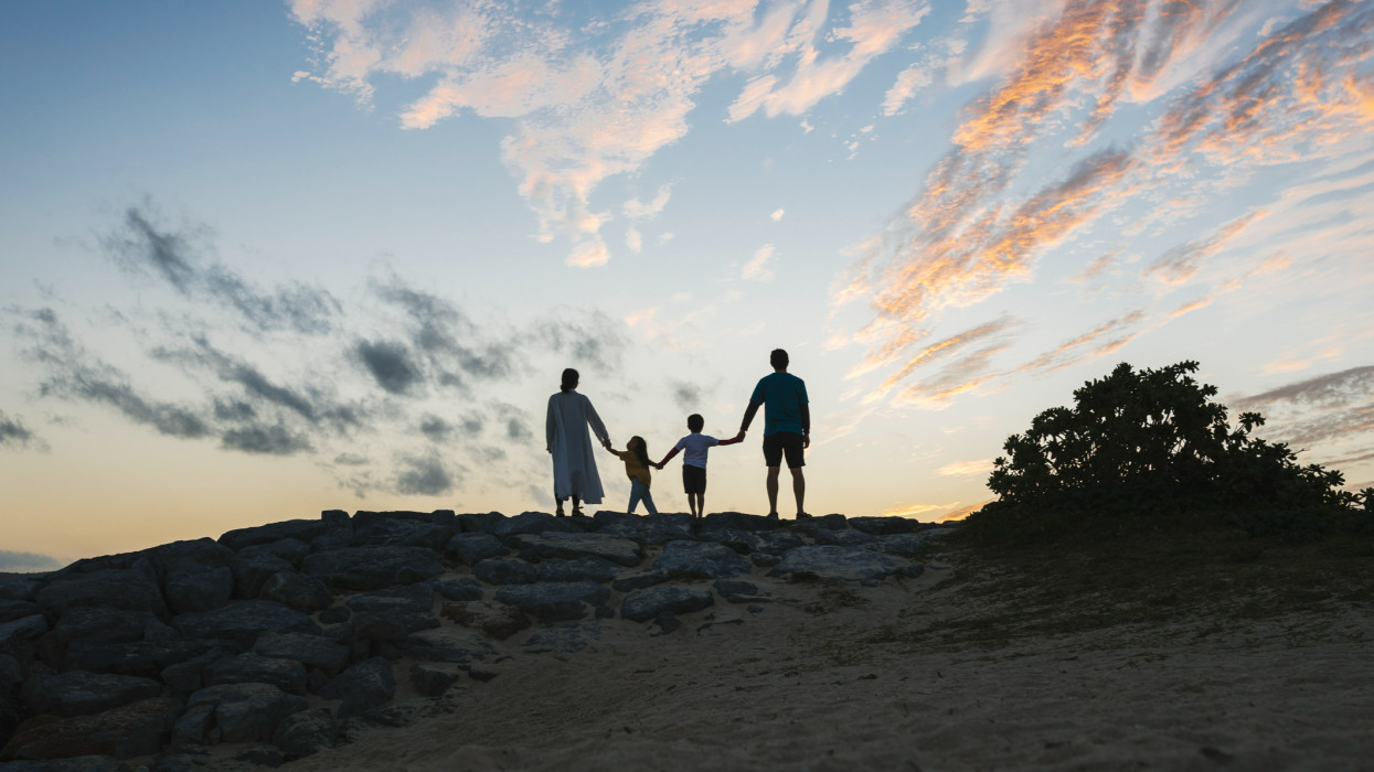 Asian father, mother, son and daughter playing in the beach in Okinawa at sunset.
