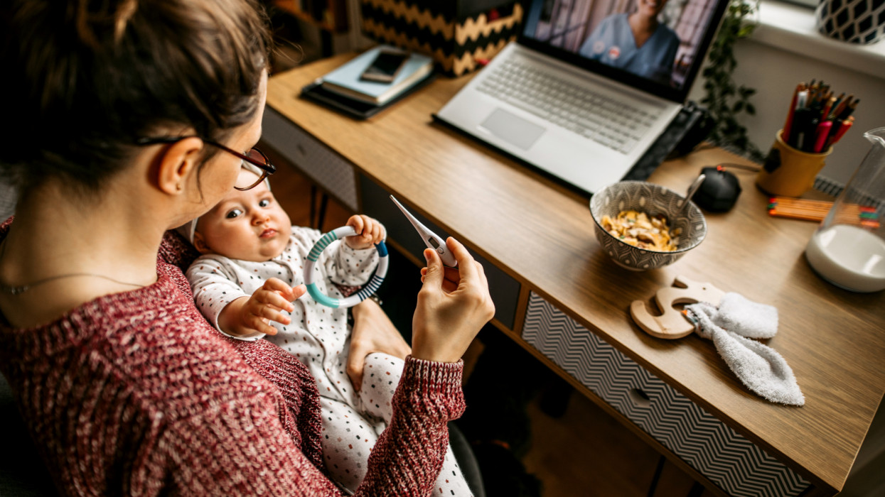 Mother holding baby girl, consulting with a doctor over a video call on a digital tablet
