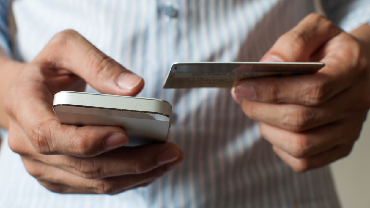 A businessman is buying online using his mobile phone and credit card