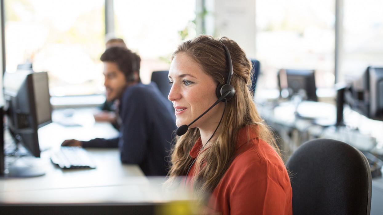 Smiling female customer representative wearing headphones working in office