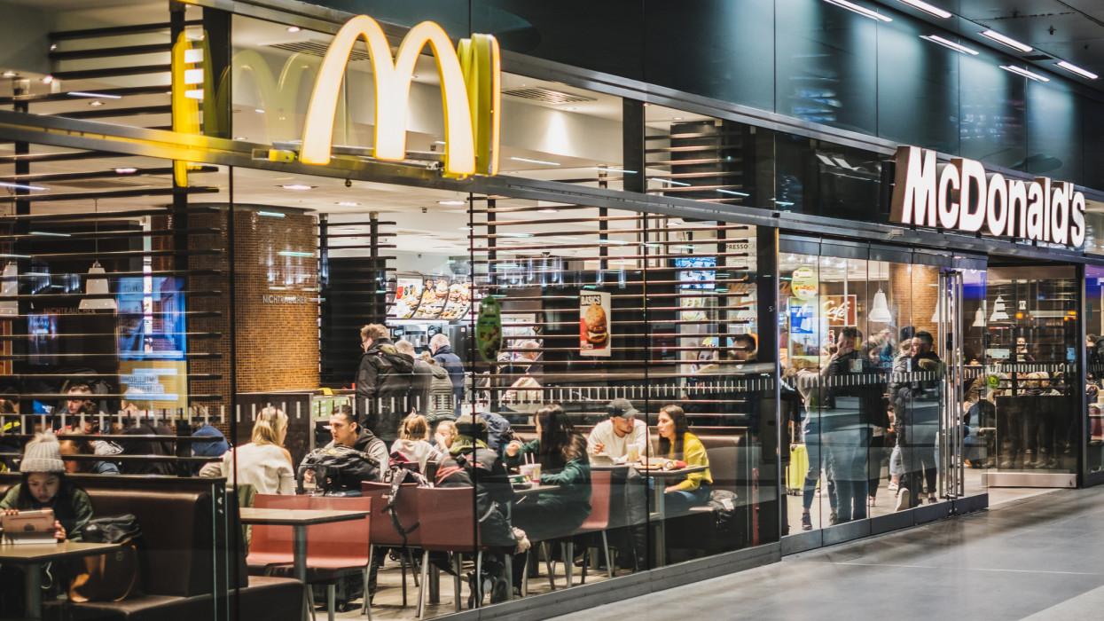 Berlin, Germany - march 2019: McDonalds and McCafe fastfood restaurant inside train stration (Berlin Hauptbahnhof).
