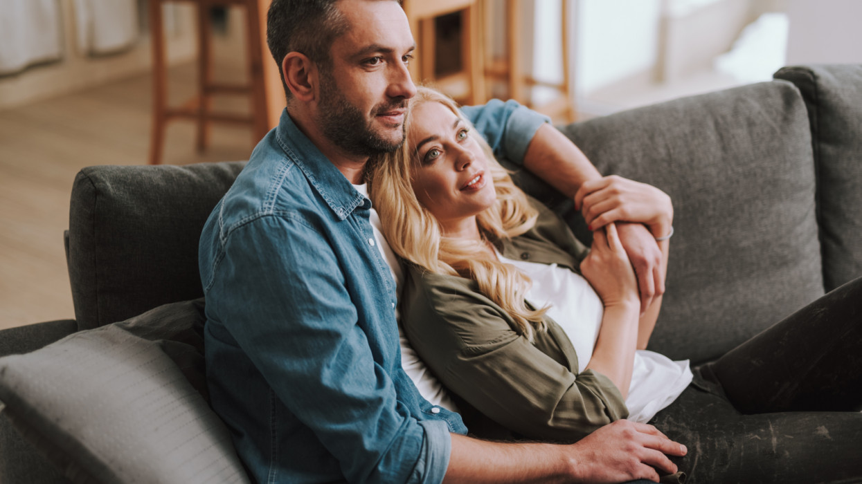 Love and happiness. Portrait of beautiful couple resting on comfortable couch at home