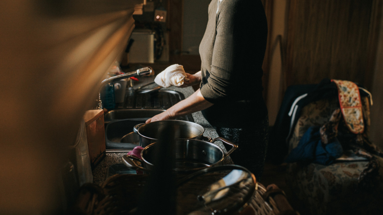 Woman at a kitchen sink, washing a dishes. Surrounded by homeware in a busy home.
