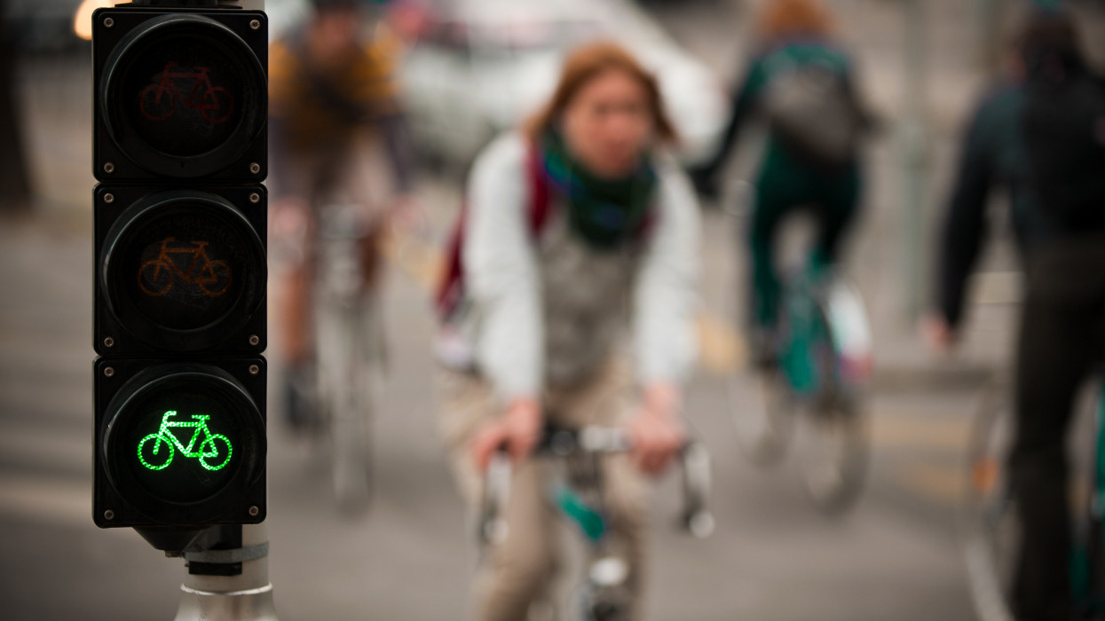 Cyclist traffic light showing green signal, with cyclists passing in the background in Budapest, Hungary.