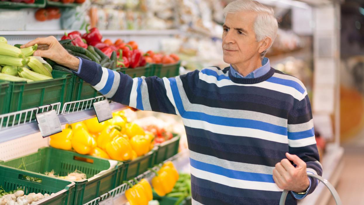 Senior man shopping fresh zucchini in grocery store