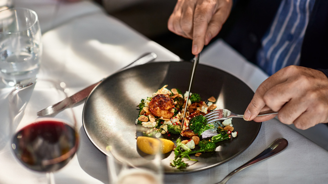 Man cutting food on plate in gourmet restaurant