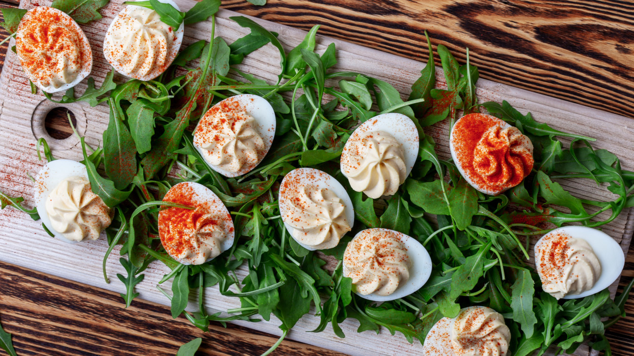 Deviled eggs with paprika on fresh arugula salad on wooden table, healthy vegetarian appetizer or snack viewed from above