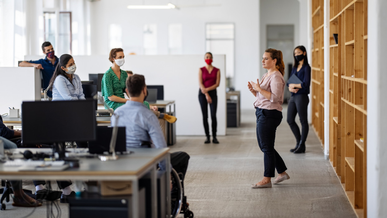 Female entrepreneur explaining new working strategies to team post-pandemic reopen. Business professionals having a meeting in the creative office after lockdown.