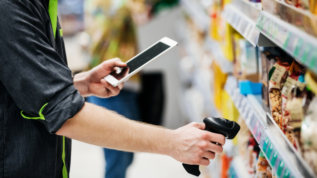 A supermarket employee keeping stock in check with digital tablet and a bar code reader.