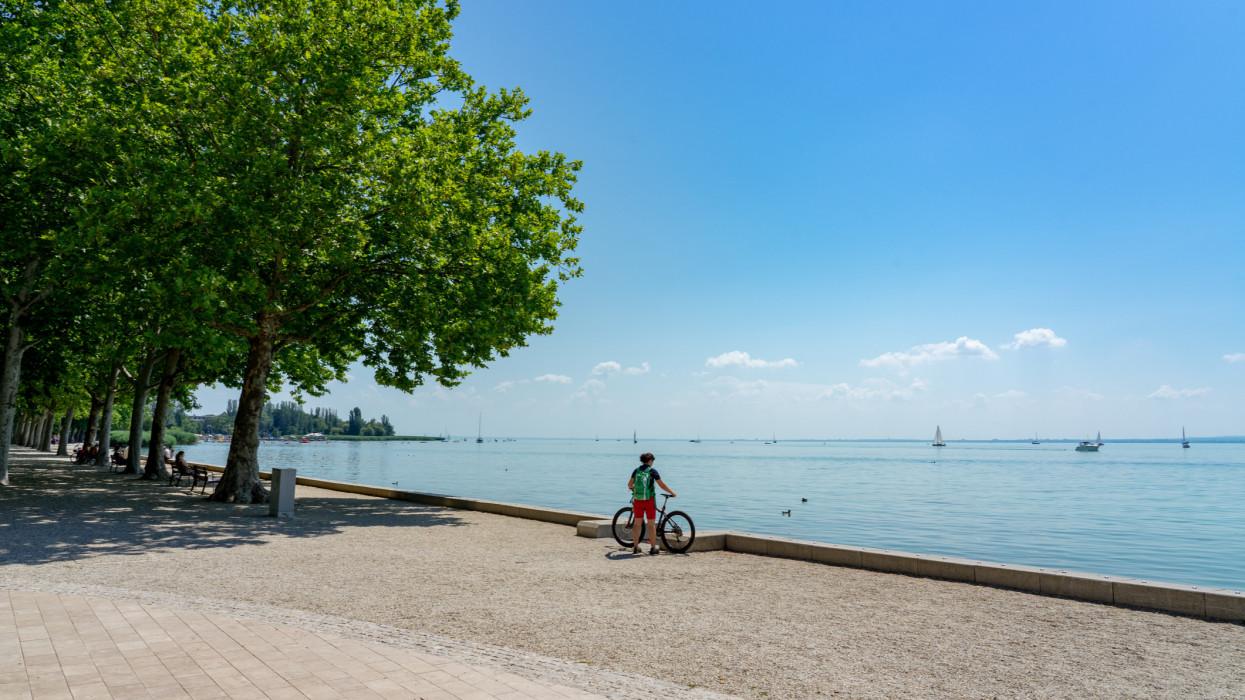 biker with her bicycle next to the Lake Balaton active holiday ride round lake .