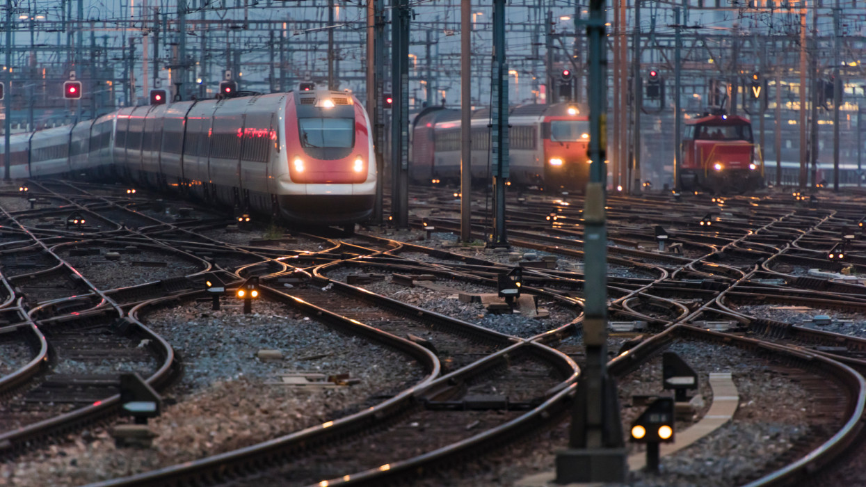 In the early morning twilight, several commuter trains are approaching a busy railway station.