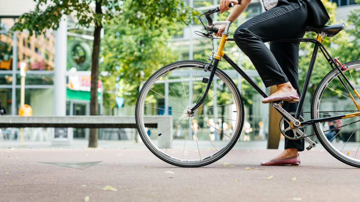 Close up shot of businesswomans legs riding a bicycle