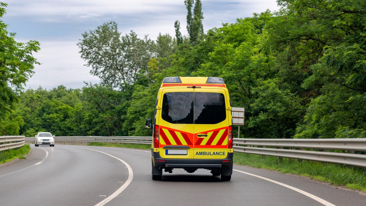 Ambulance van on the road. Bright green trees along road
