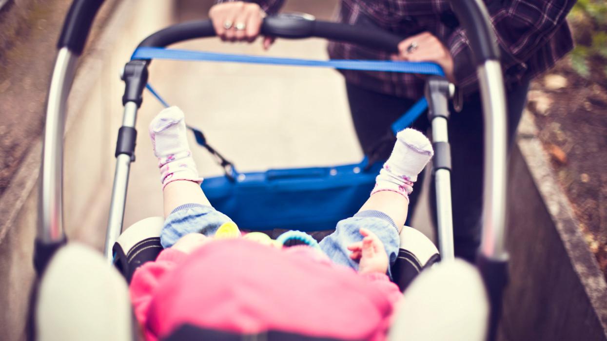 Mother pushing baby in pram.