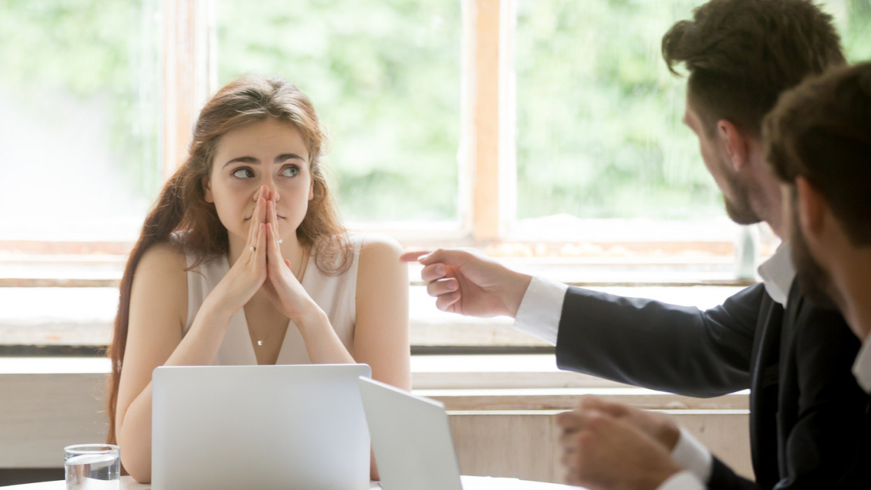 Perplexed young woman looking at coworkers pointing fingers at her. Disgruntled multiethnic team scolding female colleague who made bad work-related mistake. Stressed upset business lady in trouble. stress workplace conflict