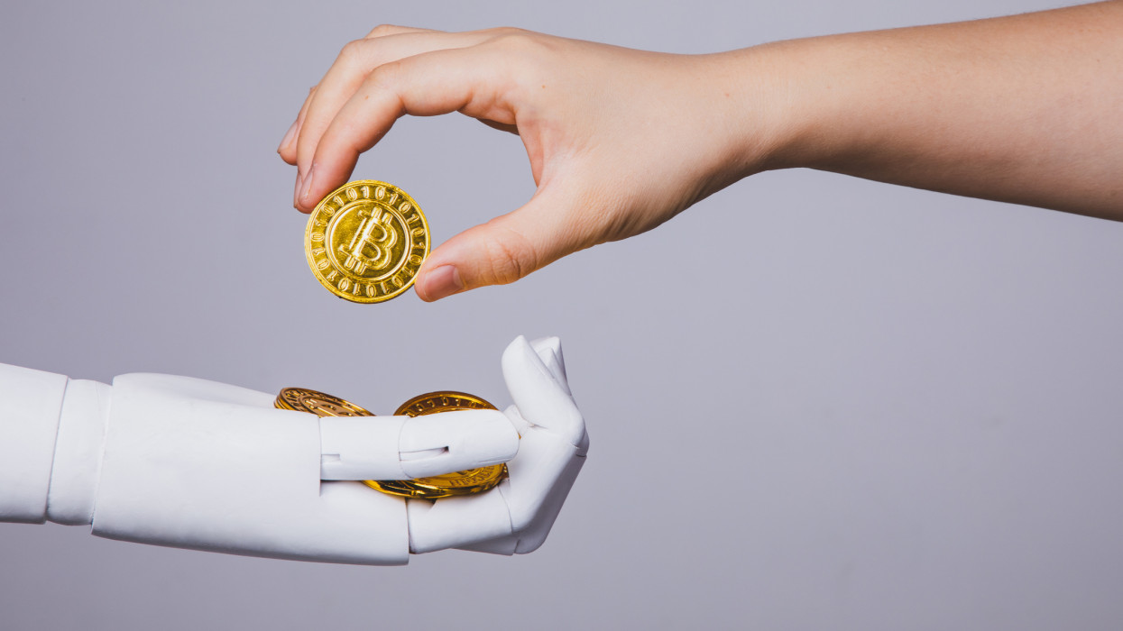 human hand taking bitcoin from robotic hand