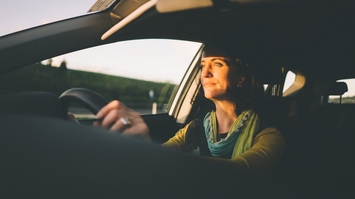 Interior shot of a woman driving a car at sunset, Melbourne