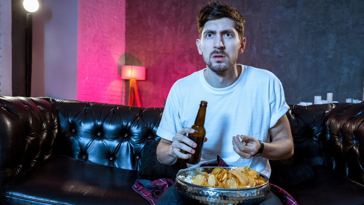 Young supporter man watching football game on television sitting at home couch with ball beer and chips in stress dejected and disappointed for failure shouting and complaining. Emotional fan watching the game of your favorite team