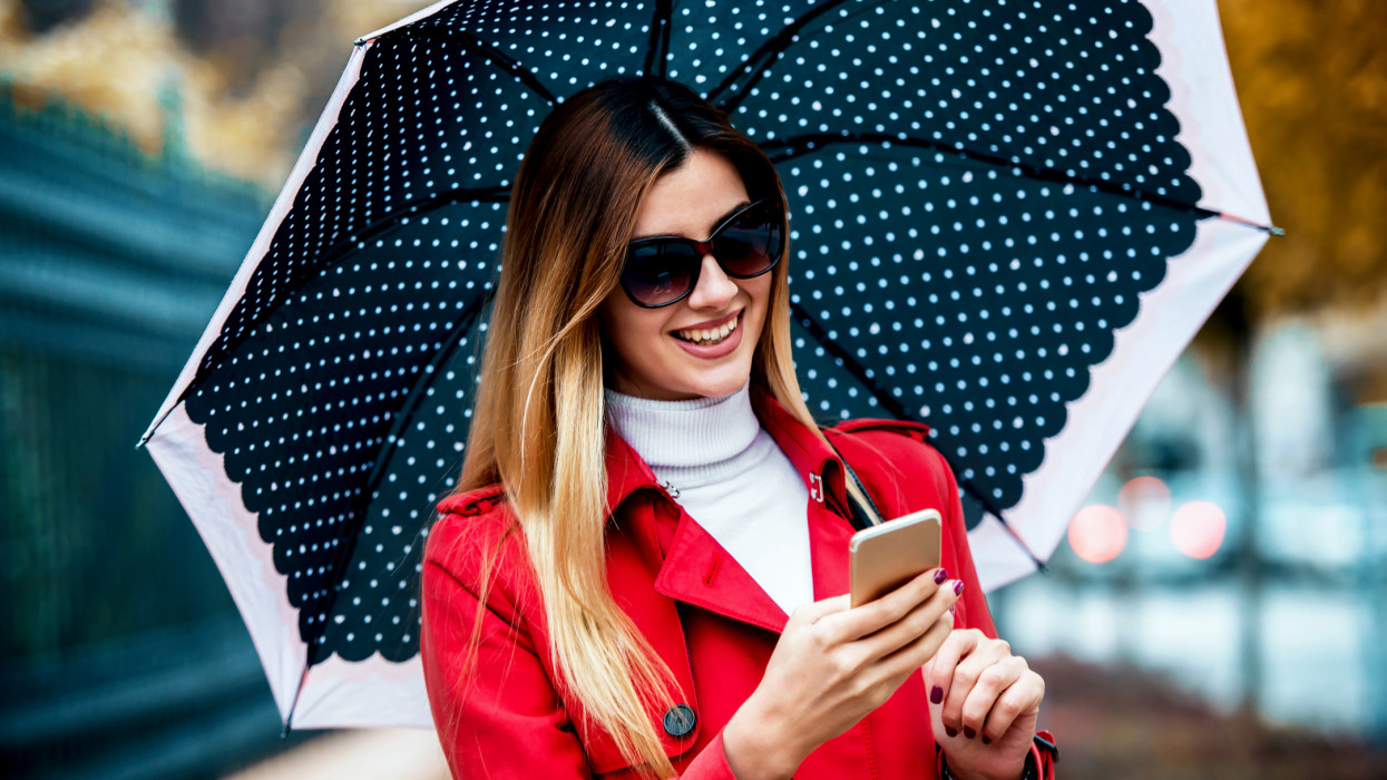 Young woman holding umbrella and browsing internet with smartphone while walking down the street. Lifestyle, technology concept