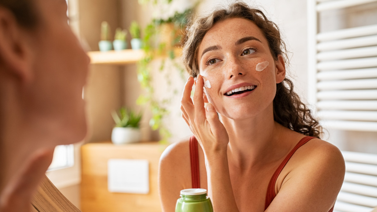 Woman caring of her beautiful skin face standing near mirror in the bathroom. Young woman applying moisturizing cream on her face during morning routine. Smiling natural girl holding little green jar of ecological cosmetic cream.