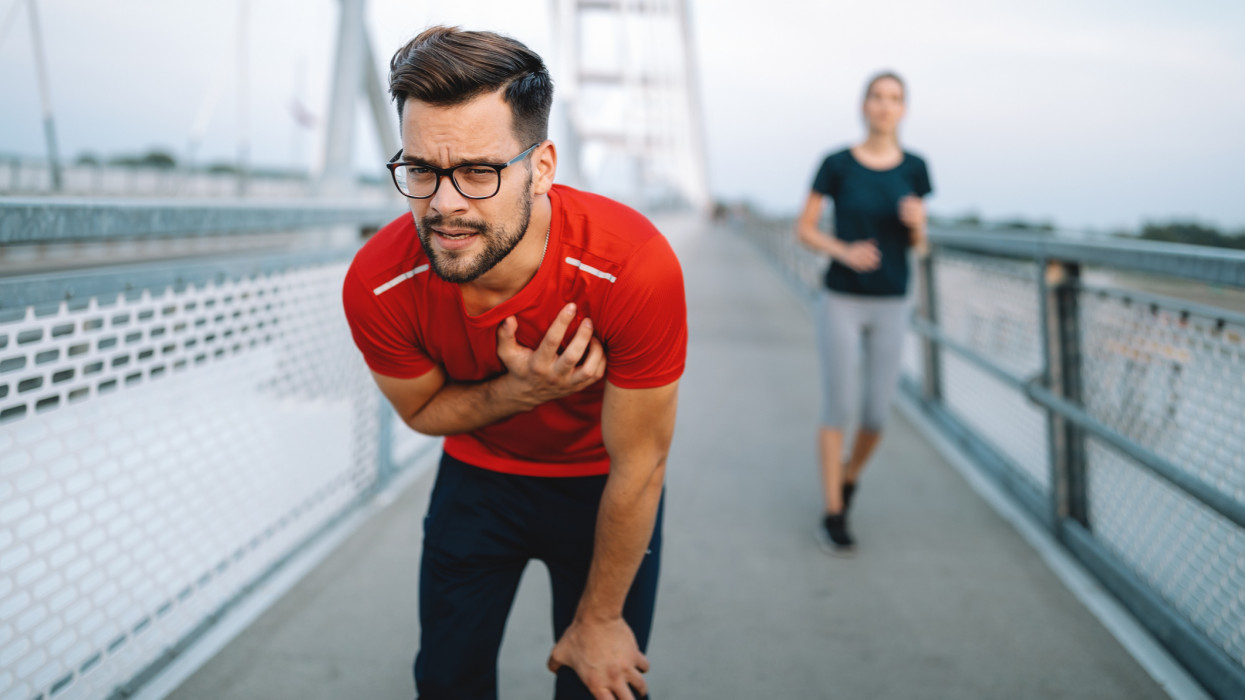 Sport fit young man having a pain in the heart area