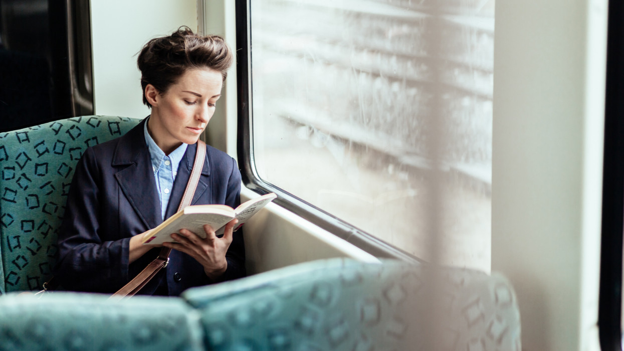 Mature businesswoman reading a book while travelling in commuter train