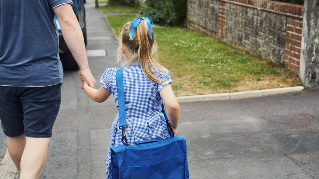 Father and daughter walking to school