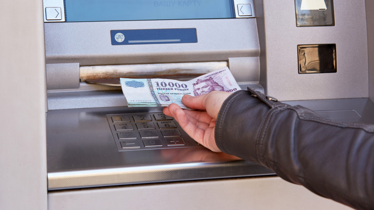 woman hand take out forint banknotes from atm