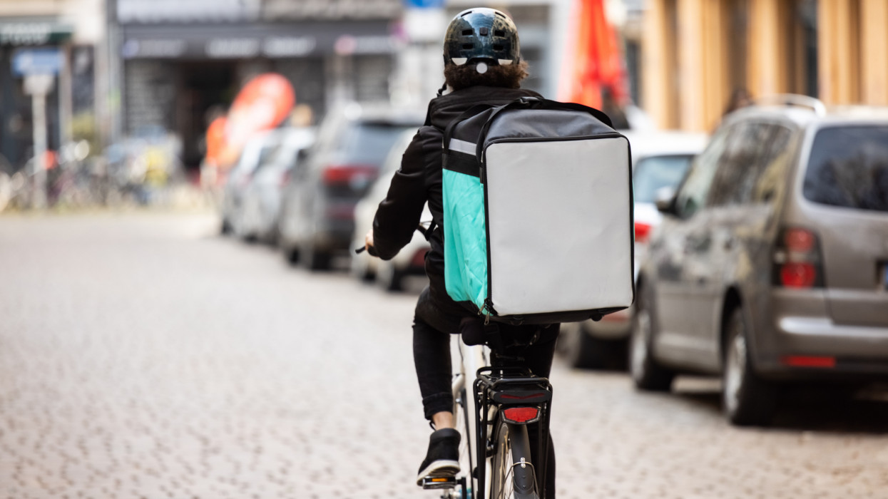 Rear view of a food delivery boy on a bike in city. Courier person riding bicycle with thermal backpack on city street for food delivery..