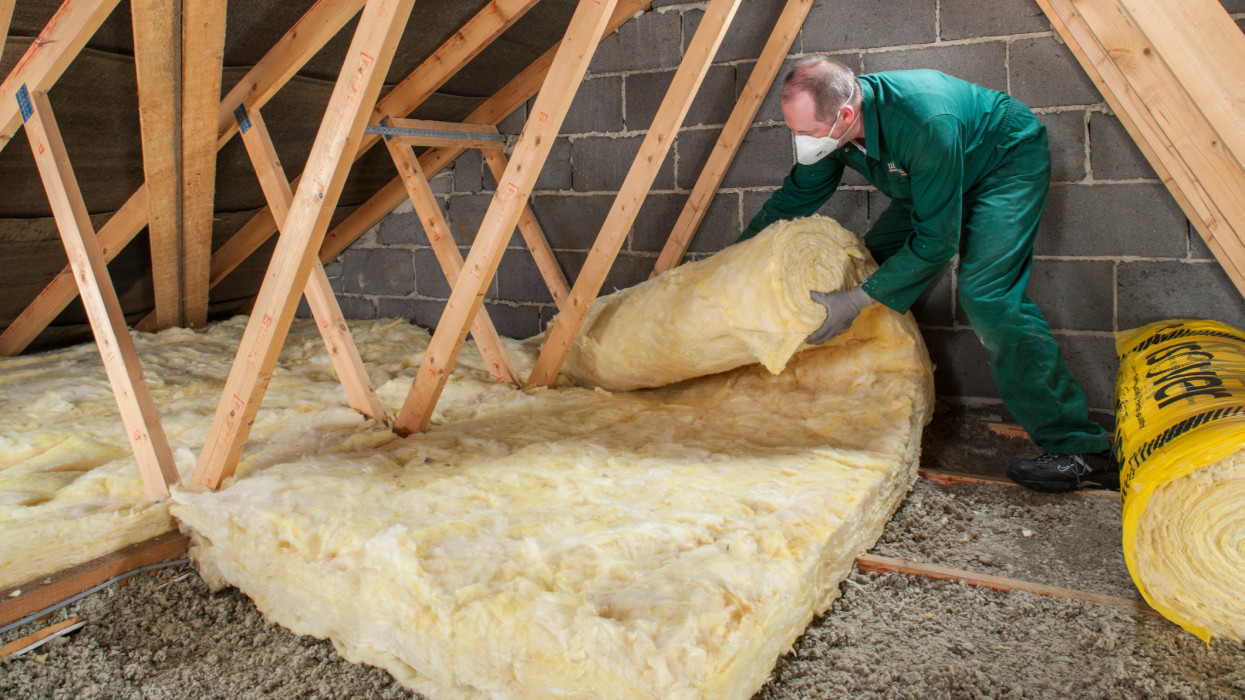 Homeowner upgrading loft insulation in domestic dwelling roof space with ceramic spun insulation blanketing.