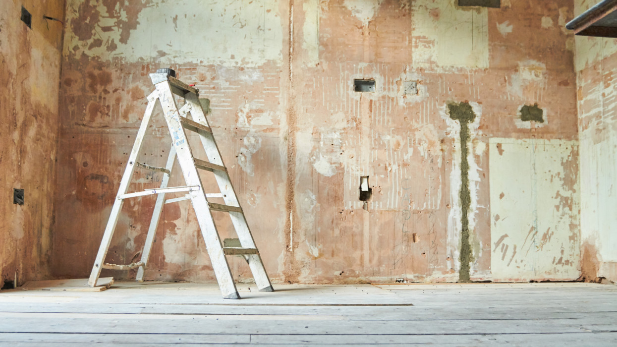 A step ladder standing in an empty domestic room mid renovation.