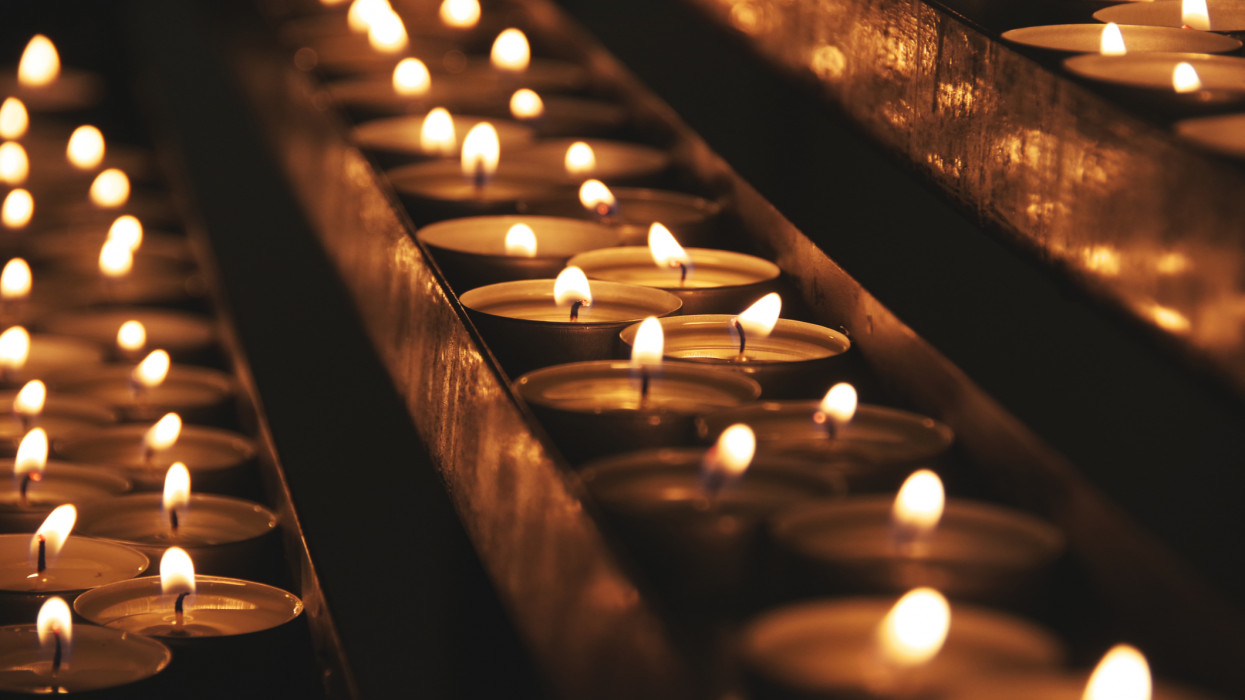 A group of lit candles on a blueish floor background in a church