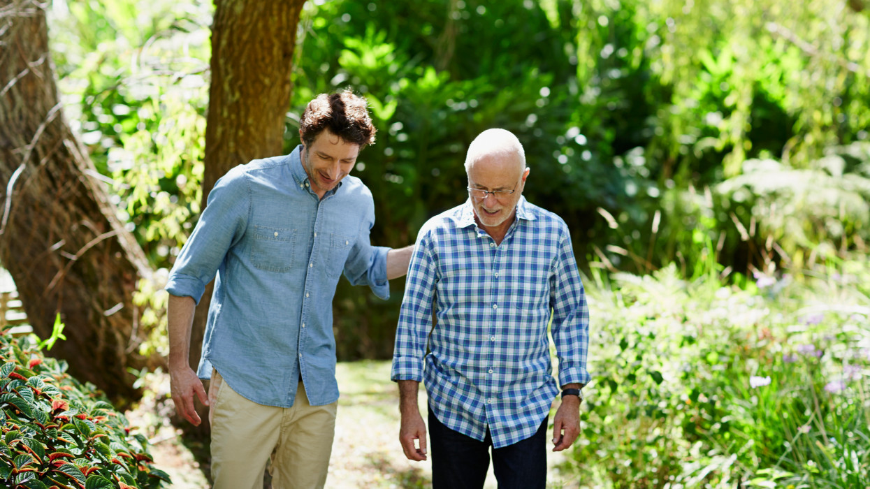 Happy senior man and son walking together in park