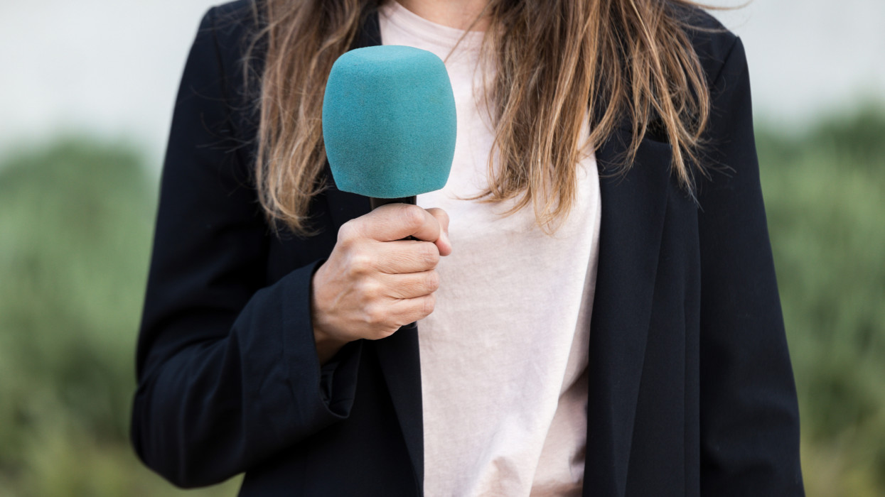 Close-up of journalist woman holding a microphone ready to broadcast the news on the street