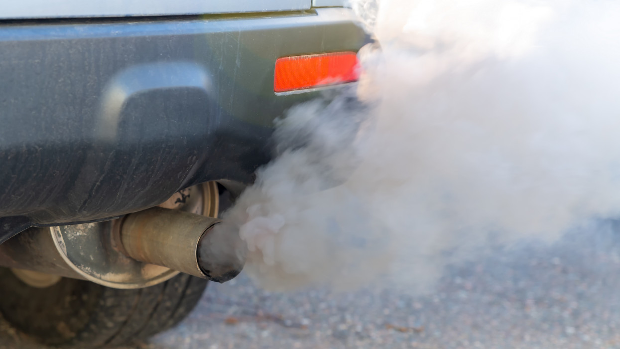 Thick smoke pours from the exhaust pile on a car. Shallow depth of field, focus on the end of the tail pipe. Closeup view.