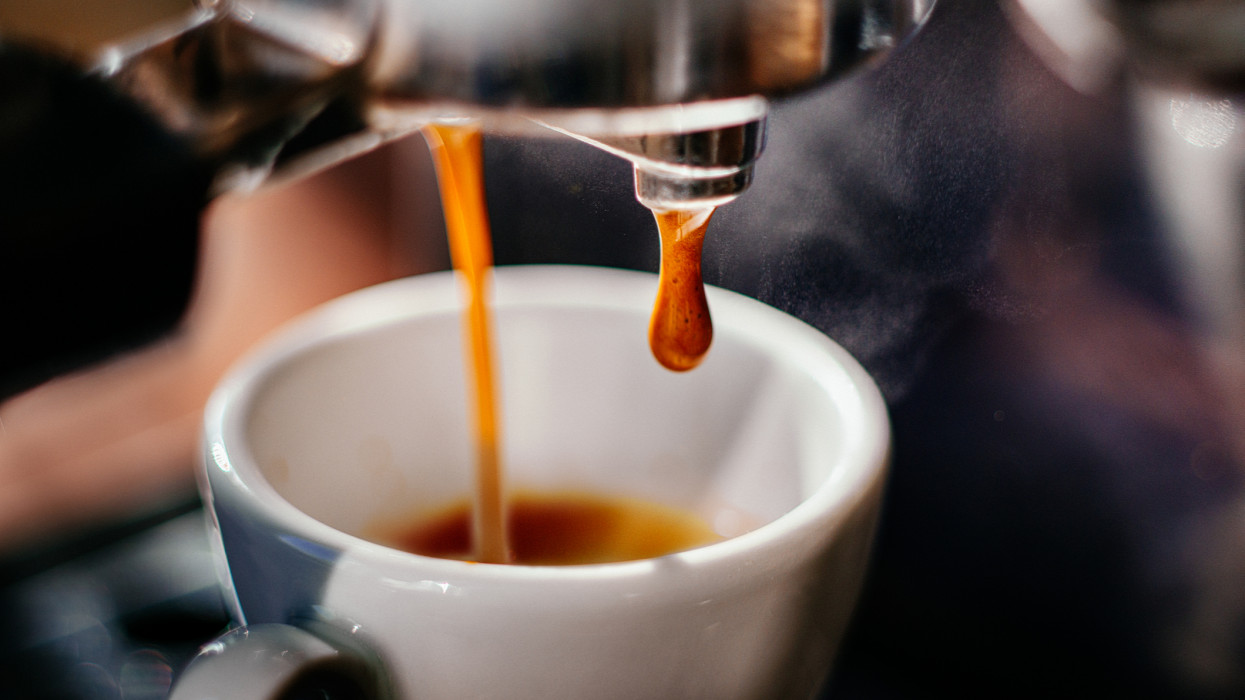Fresh espresso shot pouring out of machine.