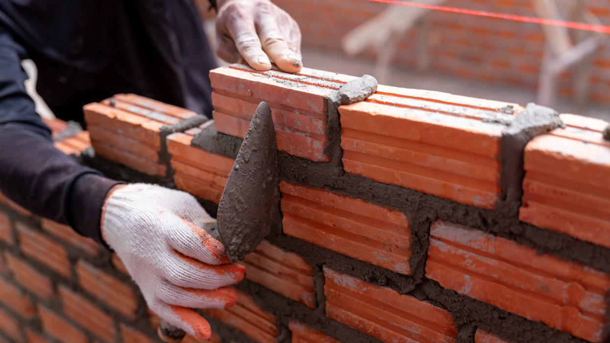 Close up hand of bricklayer worker installing bricks on construction site