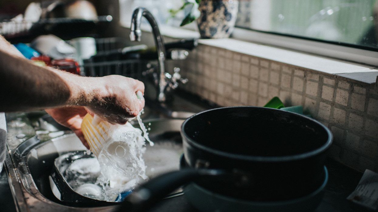 Man washing dishes at a sink.